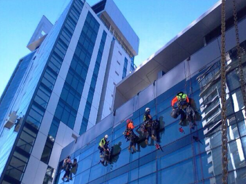 specialist height access workers abseiling a glass building