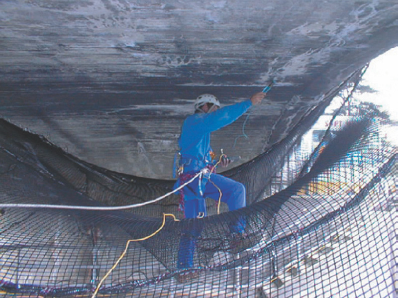 Repairing a dam wall with access ropes and safety harnesses